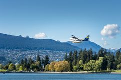 Vancouver, British Columbia, - May 5, 2019:  Harbour Air commuter plane flying West over Coal Harbour. stock photos