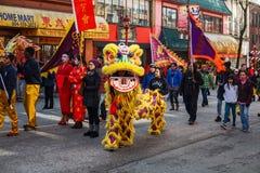 VANCOUVER, CANADÁ - 18 de febrero de 2014: La gente en Lion Costume amarillo en el Año Nuevo chino desfila en Vancouver Chinatown Imágenes de archivo libres de regalías