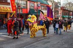 VANCOUVER, CANADÁ - 18 de febrero de 2014: La gente en Lion Costume amarillo en el Año Nuevo chino desfila en Vancouver Chinatown foto de archivo