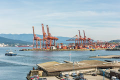 Vancouver, Canada - April 19, 2016: Industrial port with cranes, ships, cars and helicopter landing at the harbour Stock Photos