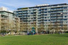 Vancouver, Canada - 9 février 2018 : Herbe verte extérieure au parc de saule près de hauts bâtiments résidentiels d'étage Image libre de droits
