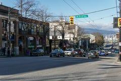 Vancouver, Canada - Februari 9, 2018: Granvillestraat en 7de Weg met mensen en de opslaggebouwen van auto'srestaurants Stock Foto's