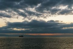 VANCOUVER, Canada - September 01, 2018: cargo ship at cloudy sunrise in strait of Georgia. VANCOUVER, Canada - September 01, 2018: cargo ship at cloudy sunrise stock photography
