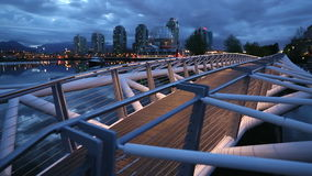 Vancouver Canoe Bridge Twilight dolly shot. The Canoe Bridge, for pedestrians, on the south side of False Creek in the early morning. Vancouver, British Columbia stock footage