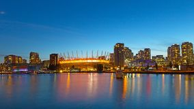 Vancouver city skyline and BC Place stadium at night in British Columbia, Canada. Illuminated modern buildings in urban settings at dusk stock images