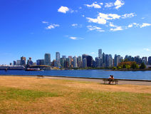 Vancouver cityscape. Vancouver downtown cityscape from Stanley Park with couple on a bench Stock Image