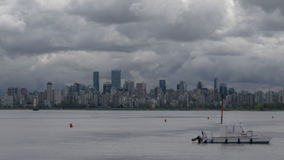 Vancouver Cityscape Cloud Timelapse pan. A pan of large, dark clouds rolling across downtown Vancouver. Timelapse stock footage