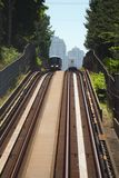 Vancouver Commuter Trains Passing. Two commuter trains pass on Vancouver's Expo Line Skytrain system. Condominium towers rise in background. British Columbia Stock Photos