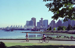 Vancouver Harbor British Columbia Canada. Couple exercise along the seawall in Stanley Park with Vancouver harbour in the background stock photos