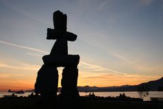 Vancouver Inukshuk Sunset. A large, stone, Inukshuk overlooking English Bay at sunset in Vancouver, British Columbia, Canada stock photo
