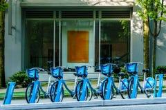 Vancouver Kanada - Maj 6, 2017, delade cyklar som parkerar i i city framme av en dräktbyggnad Royaltyfria Bilder