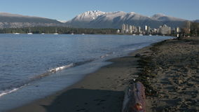 Vancouver, Mountain Snow, Kitsilano 4K slow motion. A dolly shot on Kitsilano Beach in the early morning. In the background are the snowcapped North Shore stock footage