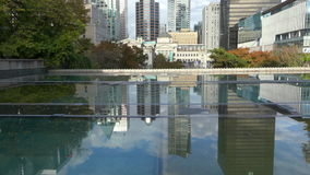 Vancouver reflected in big puddle. Tilt Vancouver Canada establishing shot downtown stock footage