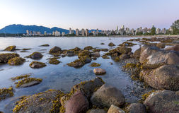 Vancouver skyline at blue hour  as seen from Kitsilano beach. Vancouver skyline at blue hour as seen from Kitsilano beach and rocks in the foreground Royalty Free Stock Image