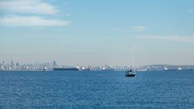 Vancouver-Skyline mit einem Segelboot und Tankern an einem sonnigen Tag lizenzfreies stockbild