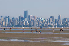 Vancouver skyline from Spanish Banks, low tide. Families enjoying the low tide from Spanish Banks with Vancouver skyline behind stock photo