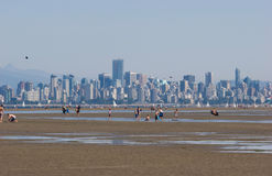 Vancouver skyline from Spanish Banks, low tide. View of Vancouver skyline and people enjoying the low tide from Spanish Banks royalty free stock image