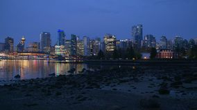 Vancouver Burrard Inlet Twilight 4K. UHD. The Vancouver skyline from the Stanley Park shoreline across Coal Harbor. British Columbia, Canada stock video footage