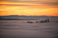 Vancouver soluppgång i dimman Driftiga högväxta byggnader upp igenom arkivfoto
