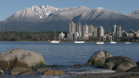 Vancouver Towers, Mountain Snow, English Bay 4K. Sailboats anchored in English Bay in the early morning. In the background are the snowcapped North Shore stock footage