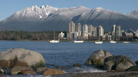 Vancouver Towers, Mountain Snow, English Bay Shore. Sailboats anchored in English Bay in the early morning. In the background are the snowcapped North Shore stock video footage