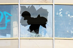 Vandal broken windows in an abandoned shopping center building that stands unguarded. Royalty Free Stock Images