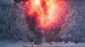 Vandal sends a flame of fire in the frozen glass. Reverse video close up stock footage