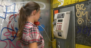 Vandalism. Calling from old dirty payphone. Woman calling from vandalized dirty old public telephone stock footage
