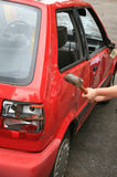 Vandalism - car hit by hammer. A red car destroyed by a hammer Stock Photos