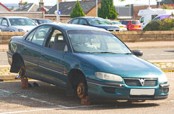 Vandalism: stolen wheels. An image of a modern saloon car whose windows have been smashed and where all four wheels have been stolen Stock Images