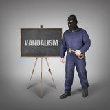 Vandalism text on blackboard with thief Stock Images