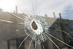 Vandalism or violence concept. Broken glass with hole royalty free stock photos