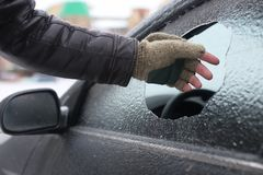Man broke the glass of the car a little stone. Vandalism winter man broke the glass of the car a little stone Stock Photos
