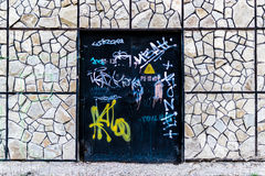 Vandalized Door and Stone Wall Stock Photo