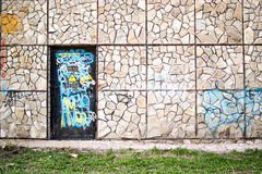 Vandalized Door and Stone Wall Stock Photography