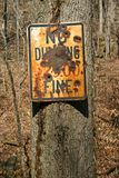 Vandalized No Dumping Sign. An old no dumping sign, full of bullet holes and rust royalty free stock photography