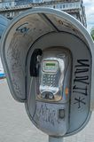 Vandalized payphone. Painted and vandalized public payphone on roadside on the city street stock image