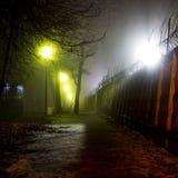 Vandringsled längs staketet med taggtråd under en tjock dimma på natten arkivfoto