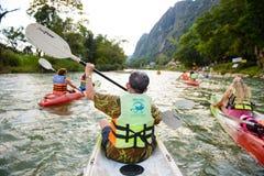 Vang Vieng,老挝- 2014年11月13日:划皮船沿Nam歌曲河的未认出的游人在Vang Vieng镇 免版税库存图片
