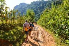 Vang Vieng,老挝- 2014年11月13日:走与泥路的旅客到Tham Nam Vang Vieng,老挝人 库存照片