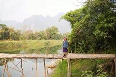 VANG VIENG,老挝- 2014年4月:人横渡的河竹子桥梁 库存照片