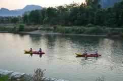 Vang Vieng,老挝- 2013年2月:游人在河乘独木舟 免版税库存图片