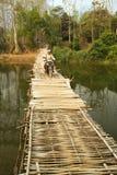 VANG VIENG,老挝- 2014年4月:通过竹桥梁摩托车的人们 免版税库存图片