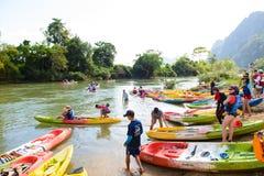 Vang Vieng, Лаос - 13-ое ноября 2014: Туристы и шлюпки каяка в реке песни Nam на Vang Vieng, Лаосе Стоковые Изображения
