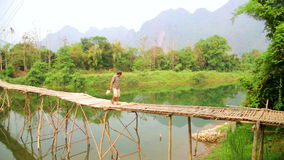 VANG VIENG, LAOS - APRIL 2014: crossing river on bamboo bridge. VANG VIENG, LAOS - APRIL 2014: People crossing river on bamboo bridge stock video footage
