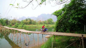 VANG VIENG, LAOS - APRIL 2014: passing bamboo bridge by motorbike. VANG VIENG, LAOS - APRIL 2014: people passing bamboo bridge by motorbike stock footage