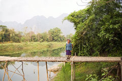 VANG VIENG, LAOS - APRIL 2014: People crossing river bamboo bridge Stock Photos