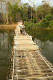 VANG VIENG, LAOS - APRIL 2014: people passing bamboo bridge motorbike Royalty Free Stock Images