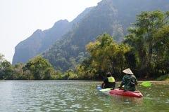 Vang Vieng, Laos - 16 de febrero de 2016: Los turistas no identificados están remando los barcos del kajak en el río de la canció Foto de archivo
