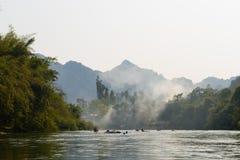 Vang Vieng, Laos - 16 de febrero de 2016: Remo de los turistas el kayaking entre las montañas en el río de la canción de Nam el 1 Fotos de archivo